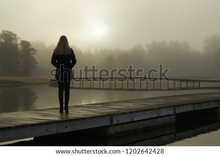 Young woman standing alone on lake footbridge and staring at sunrise in gray, cloudy sky. Mist over water. Foggy air. Early chilly morning. Dark, scary moment and gloomy atmosphere. Back view. Royalty-Free Stock Photo #1202642428