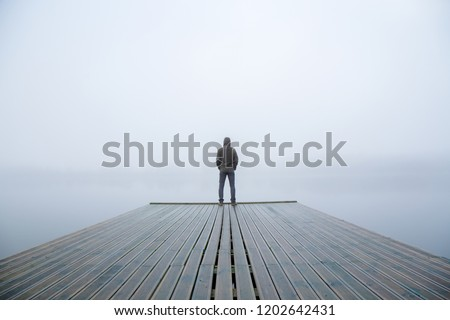 Young man standing alone on edge of footbridge and staring at lake. Mist over water. Foggy air. Early chilly morning in autumn. Beautiful freedom moment and peaceful atmosphere in nature. Back view. #1202642431