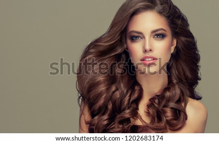 Young, brown haired woman with voluminous hair.Beautiful model with long, dense, curly hairstyle .  #1202683174