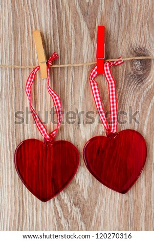 two red glass hearts hanging on rope #120270316