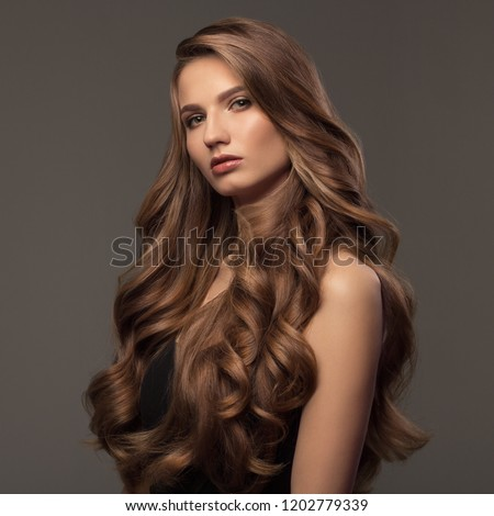 Beautiful woman with brown curly hair. Hairstyle. #1202779339