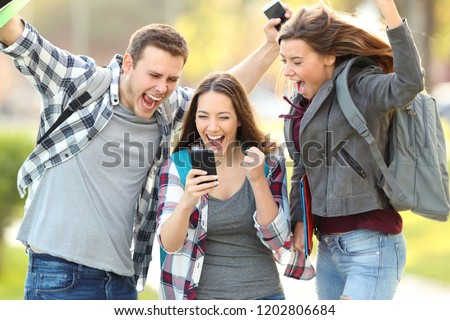 Three excited students checking exam grades online in a smart phone #1202806684