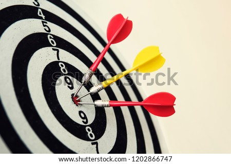 Side view of a dartboard with three darts in the bull's eye. Well-aimed dart throwing. Triple bull's-eye hit. Three well-made dart throws. Successful attempts. To attempt difficult task. Darts ace #1202866747