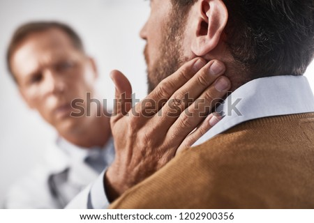 Close up of adult doctor probing occipital lymph nodes with circular movements of his fingers Royalty-Free Stock Photo #1202900356