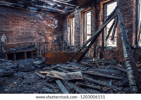 Burned house interior after fire, ruined building room inside, disaster or war aftermath concept #1203006151