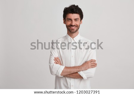Studio shot of a smiling attractive young man wearing white shirt looks happy and friendly keeps arms crossed isolated over white background #1203027391