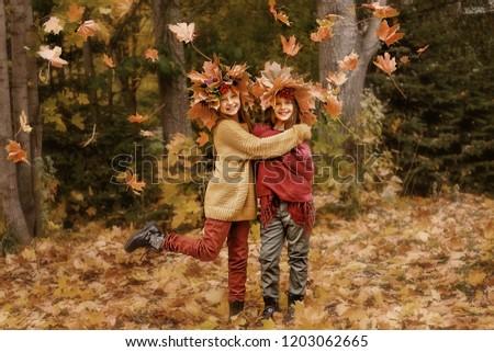 two girls having fun in autumn leaves #1203062665