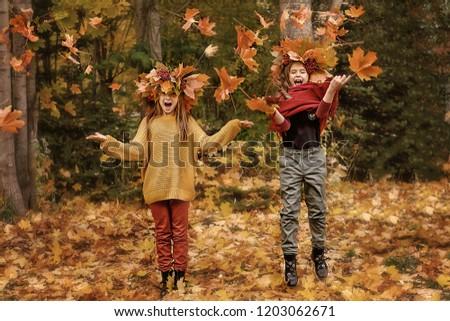 two girls having fun in autumn leaves #1203062671