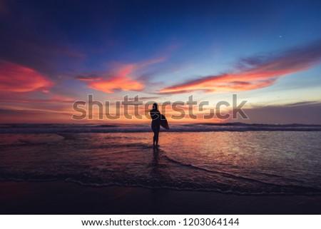 Girl walking in sunshine in warm evening sun holding surfboard. Water sport summer vacation travel concept. Bali, Indonesia #1203064144