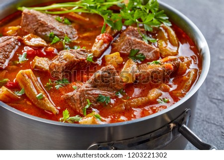 overhead view of hearty Beef and Okra Stew in a metal casserole on a concrete table, view from above, close-up