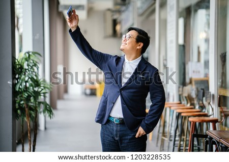 A handsome middle-aged Chinese Asian man is taking a selfie of himself in the city. He is dressed in smart casual and is wearing a polo, jacket and jeans.  #1203228535