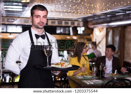 Portrait of frendly male waiter who is standing with tray in restaurant. #1203375544