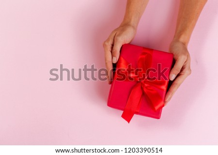 Woman holding gift box on color background #1203390514
