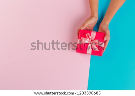 Woman holding gift box on color background #1203390685