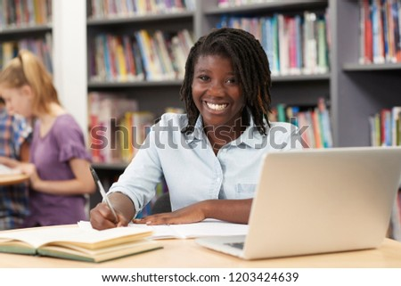 Portrait Of Female High School Student Working At Laptop In Library #1203424639