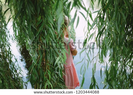 little girl standing inside the branches of weeping willow #1203444088