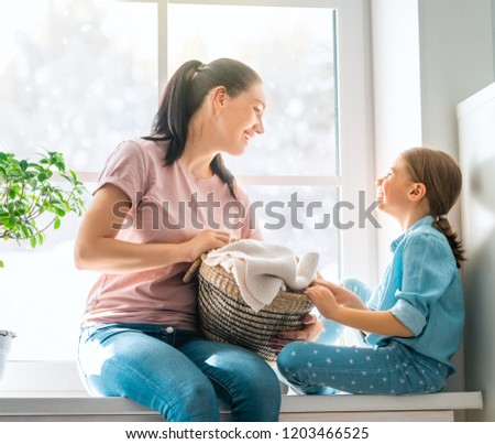 Beautiful young woman and child girl little helper are having fun and smiling while doing laundry at home. #1203466525