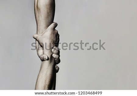 Helping hand concept and international day of peace, support. Helping hand outstretched, isolated arm, salvation. Close up help hand. Two hands, helping arm of a friend, teamwork. Black and white. Royalty-Free Stock Photo #1203468499