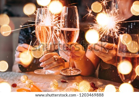 Friends celebrating Christmas or New Year eve party with Bengal lights and rose champagne. #1203469888