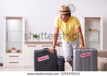 Man going on vacation with fragile suitcases #1203478216
