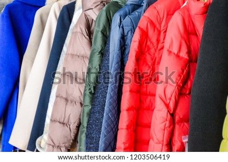 Coats and jackets on hangers in the store. Sale of outerwear Royalty-Free Stock Photo #1203506419