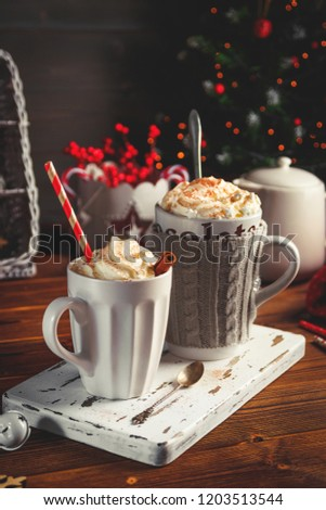 Cozy Christmas composition.Two mug with hot drinks, chocolate with whipped cream and cappuccino with cinnamon stick on a dark wooden background. Sweet treats for cold winter days. #1203513544