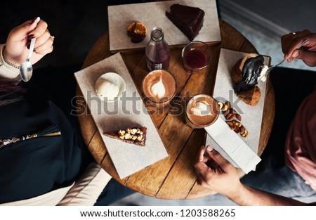 High angle of a diverse group of young friends sitting together around a cafe table enjoying an assortment of desserts and coffee #1203588265