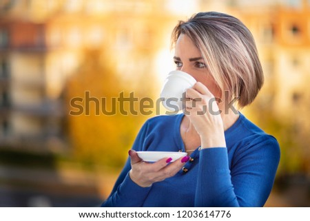 A woman drinking from a cup #1203614776