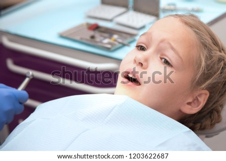 Close-up of little girl opening her mouth wide during inspection of oral cavity #1203622687