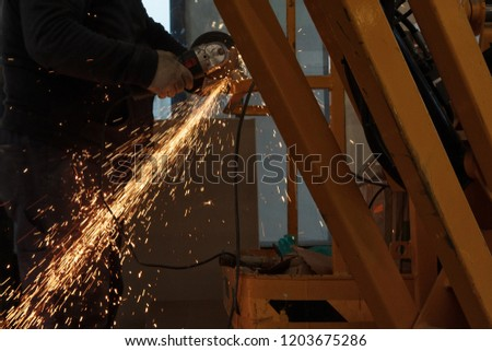 worker grinding cutting metal sheet with grinder machine and sparks #1203675286