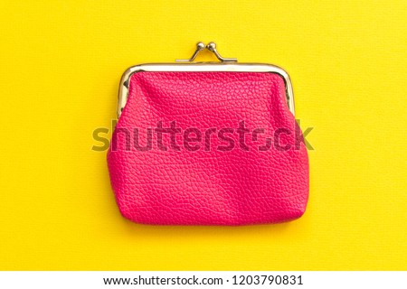 Pink wallet on yellow background . Close up. Top view. Royalty-Free Stock Photo #1203790831