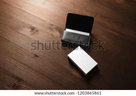 Black leather card holder with blank white business cards on wood table background.