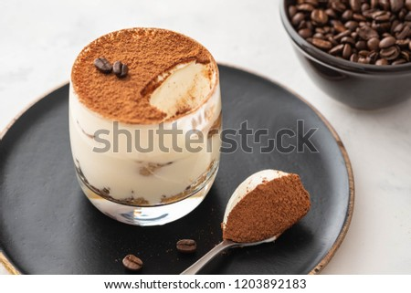 Delicious Italian dessert tiramisu, chocolate, cocoa and coffee beans on a black background. Copy space. #1203892183