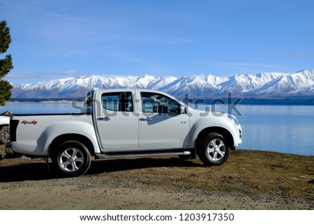 Pickup truck parked by mountain lake in New Zealand July 2018  #1203917350