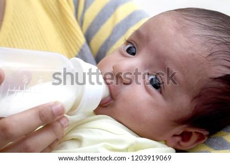 Mother feeding milk to newborn baby #1203919069