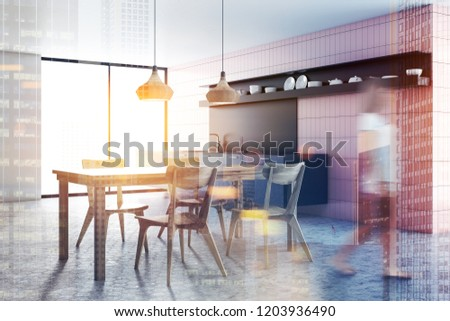 Woman walking in interior of modern kitchen with pink tile walls, gray countertops, long wooden table with chairs and stylish ceiling lamps. Toned image double exposure blurred #1203936490