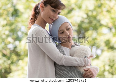 Mother hugging sad daughter with cancer #1203943921