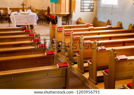 Empty wooden church benches of a Christian church with bible or choir books with cross . Blurry alter in the background. Selective focus. Concept of church service or empty churches. #1203956791