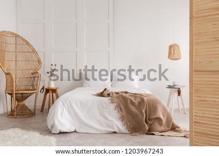 Rattan chair and wooden table next to bed with brown blanket in white bedroom interior. Real photo Royalty-Free Stock Photo #1203967243