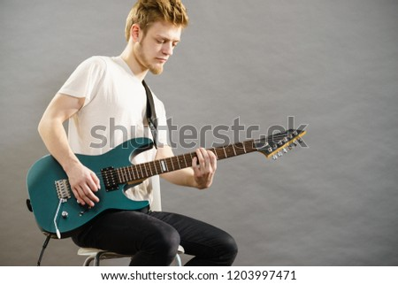 Man playing on electric guitar during gig. Musical instrument. Teenage boy having music hobby. #1203997471