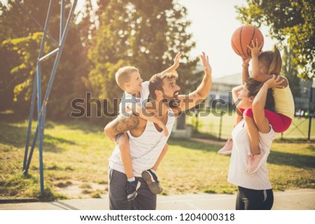 Little player on mother shoulders. Family playing basketball. #1204000318
