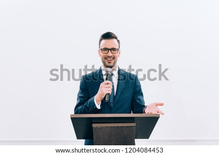 smiling speaker gesturing and talking into microphone at podium tribune during seminar in conference hall Royalty-Free Stock Photo #1204084453