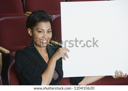 Portrait of happy African American businesswoman holding blank placard while sitting in auditorium #120410620