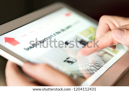 Man searching holiday home, vacation apartment or property for rent online with tablet. Person thinking of buying new house on internet. Finding rental flat. Real estate website. Investment research.