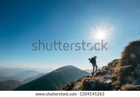 Boy backpacker traveler walk up on mountain top in contrast sun light Royalty-Free Stock Photo #1204145263