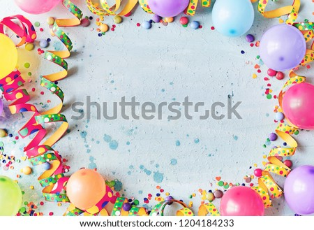 Multicolored carnival or birthday background on blue with a frame of colorful party balloons, streamers, confetti and candy around central copy space #1204184233