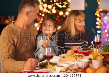 Happy family having Christmas dinner at home #1204197871