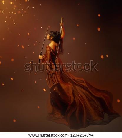 beautiful warior princess  dark hair Japanese samurai woman, young sexy girl light long red silk fly fabric fluttering dress open back holds katana. art photo background sparkle  divine sun magic fire