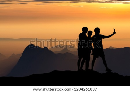 silhouette of people taking selfie at the cliff on mountains with sunset in the evening #1204261837