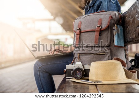 Summer day of Asian woman sitting using laptop at train station. She have camera film, Backpack, hat, map and smartphone. Travel and work freelance concept. hipster style. Royalty-Free Stock Photo #1204292545